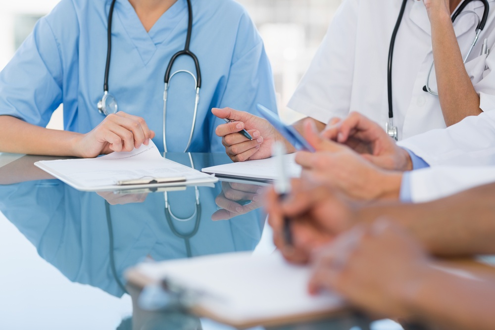 Mid section group of young doctors in a meeting at hospital.jpeg